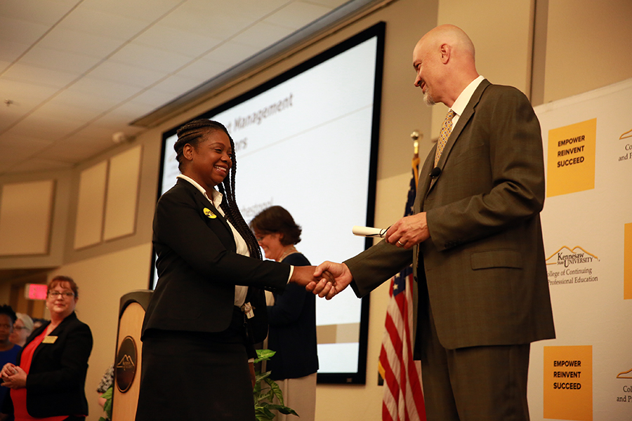 Treshun Randolph shakes Dean Tim Blumentritt's hand as she crosses the stage, marking her graduation from the Project Management Certificate program.