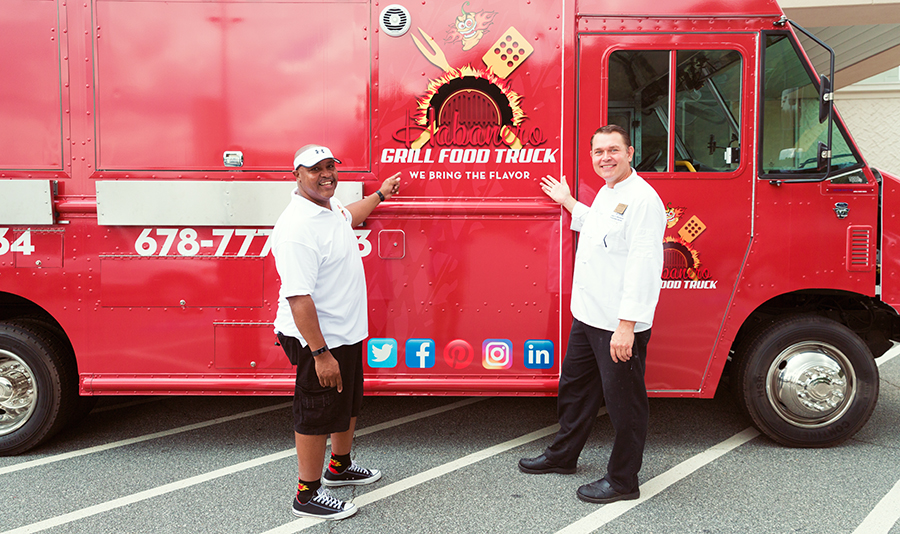 Culinary Apprenticeship graduate David Johnson shows Chef Robert Gerstenecker his new food truck during a visit to the College of Continuing and Professional Education.