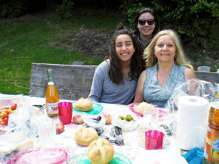 Mary Ann McCoy and another teacher and TESOL graduate, Nicole Bezerra, with her daughter Lilia enjoy lunch in the Italian Alps.
