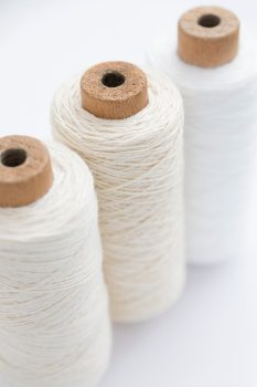 Three spools of white thread for sewing