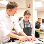 Chef Robert Gerstenecker assists a student in the Academy for Learning and Social Growth with knife skills in the KSU Center Culinary kitchen