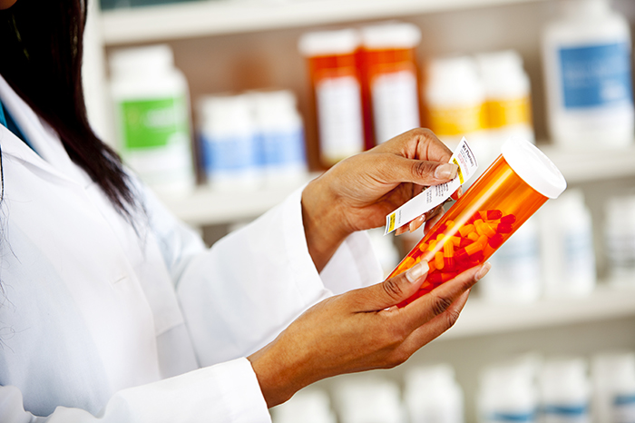 A pharmacy technician places a label on a medication bottle