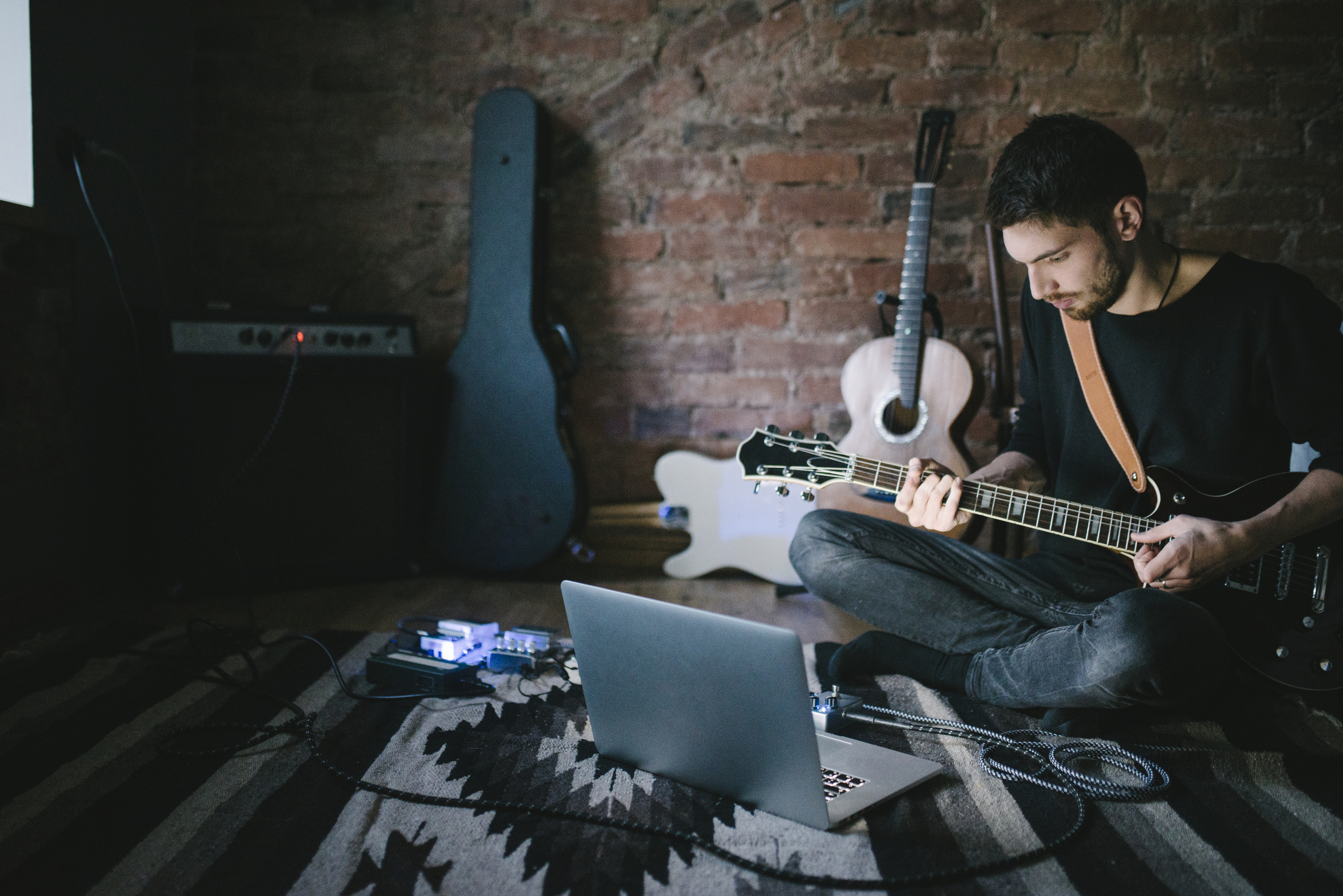 Young Musician Playing Guitar Sitting in front Notebook
